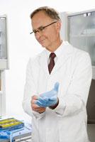 Male dentist putting on glove