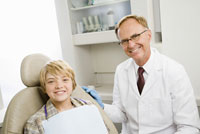 Male dentist and boy in dentists office