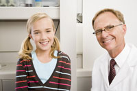 Male dentist and girl in dentists office