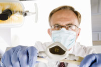 Male dentist holding oxygen mask