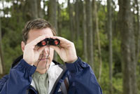 Man looking through binoculars 11029014465| 写真素材・ストックフォト・画像・イラスト素材|アマナイメージズ