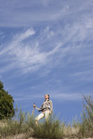 Low angle view of woman on hill 11029014486| 写真素材・ストックフォト・画像・イラスト素材|アマナイメージズ