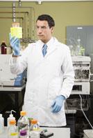 Male scientist examining vials
