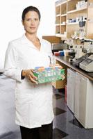 scientist holding tray of vials