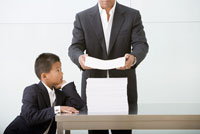 Father and son with stack of paperwork