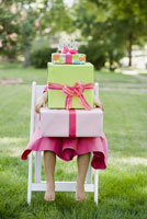 Girl sitting with stack of gifts