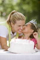 Mother bringing daughter birthday cake