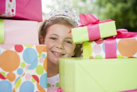 Girl behind stack of gifts