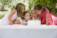 Girls blowing out birthday candles