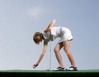 Woman placing golf ball on tee 11029014727| 写真素材・ストックフォト・画像・イラスト素材|アマナイメージズ