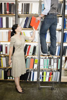 woman handing book to co-worker