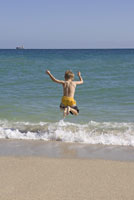 boy jumping in ocean