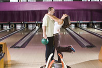 Couple kissing in bowling alley