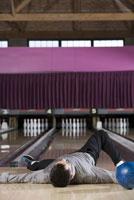 Man laying with bowling ball 11029015190| 写真素材・ストックフォト・画像・イラスト素材|アマナイメージズ