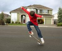 Boy skateboarding on residential street 11029015214| 写真素材・ストックフォト・画像・イラスト素材|アマナイメージズ