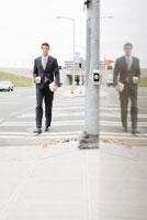 Businessman walking across street
