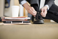Businessman tying shoe