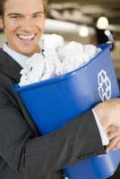 Businessman carrying recycling bin
