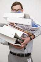 Businessman carrying stack of binders