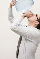 man drinking from water cooler bottle