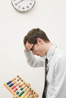 Businessman looking at abacus