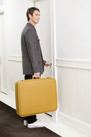 Man with suitcase opening room door