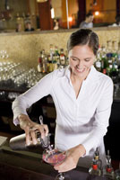 Female bartender pouring cocktail