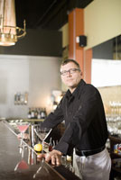Male bartender leaning on bar