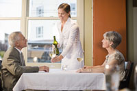 Waitress serving wine to couple