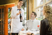 Waitress opening bottle of wine