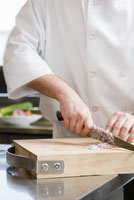 Male chef chopping onion