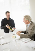 Waiter showing wine bottle to man