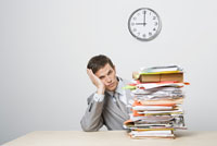 Businessman next to stack of paperwork