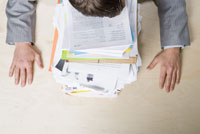 man resting head on stack of paperwork