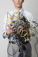 man holding tangle of computer wires