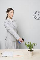 Businesswoman watering plant 11029015760| 写真素材・ストックフォト・画像・イラスト素材|アマナイメージズ