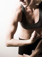 Woman flexing biceps muscle 11029015915| 写真素材・ストックフォト・画像・イラスト素材|アマナイメージズ