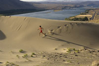 Woman running down sand dune