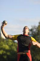 Male athlete throwing shot put
