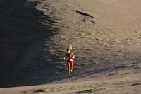 Woman running on sand dunes 11029016091| 写真素材・ストックフォト・画像・イラスト素材|アマナイメージズ