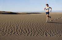 Woman running on sand dunes 11029016096| 写真素材・ストックフォト・画像・イラスト素材|アマナイメージズ