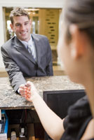 Businessman paying at hotel front desk