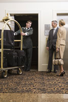 Bellhop pulling luggage cart 11029016338| 写真素材・ストックフォト・画像・イラスト素材|アマナイメージズ