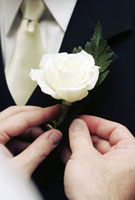 Man fastening boutonniere to lapel