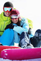 Snowboarder couple sitting on snow