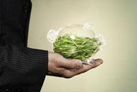 Businessman holding piggy bank filled with grass 11029016638| 写真素材・ストックフォト・画像・イラスト素材|アマナイメージズ