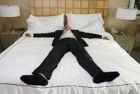 Clothed businessman sleeping in bed