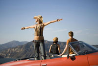 Woman standing in backseat of convertible in scenic area