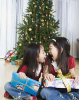 Asian sisters opening Christmas presents