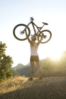 Woman lifting mountain bike over head
